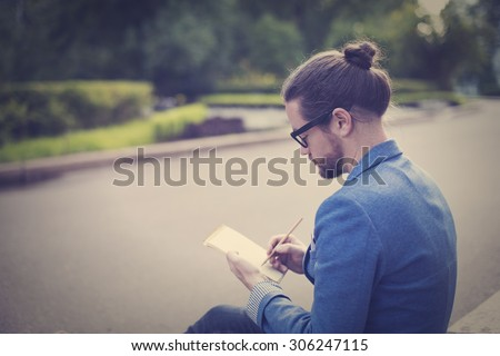 A bearded man in a jacket and sunglasses drawing or writing something in pencil on notebook. - stock photo