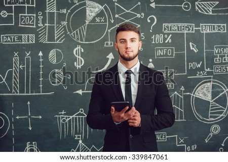 A bearded man in a suit standing with tablet near whiteboard with graphs - stock photo