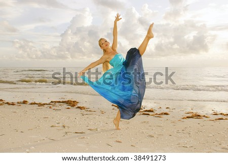 A beautiful adult female ballerina is dancing on the beach with her leg kicked up high looking at you the viewer with a fairy tale look in classic ballet pose. - stock photo