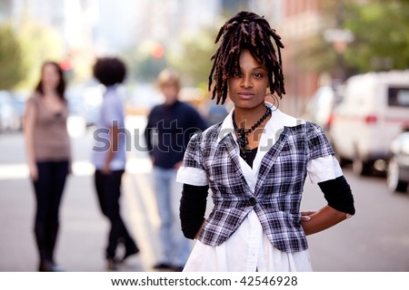 A beautiful african american woman in a city setting with friends - stock photo
