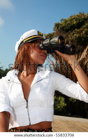 a beautiful african american woman in a short skirt and a captains hat at the beach with binoculars - stock photo