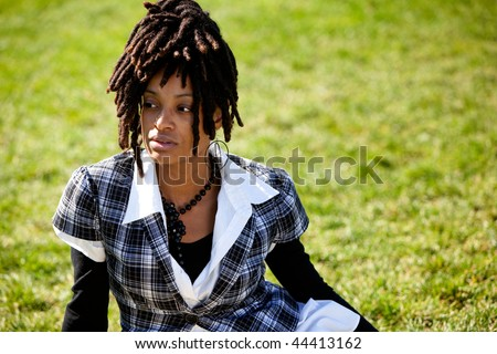 A beautiful African American woman isolated on grass - stock photo
