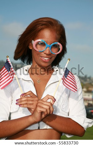a beautiful african american woman wears american flag glasses and waves american flags for the 4th of july - stock photo