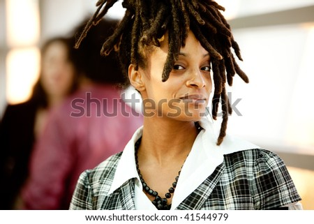 A beautiful African American woman with friends in background - stock photo