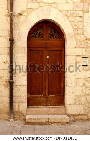 A beautiful ancient wooden door with decorated glass part of on old house in Italy.