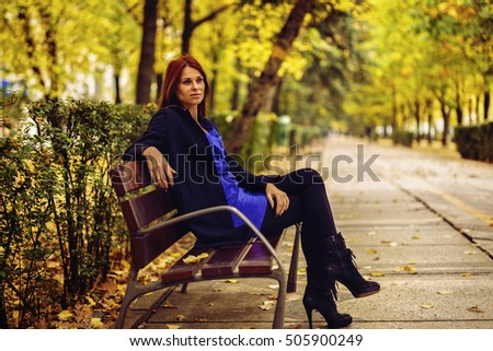 a beautiful and elegant woman on the bench in autumn park