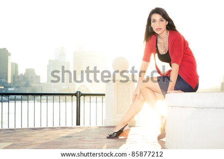 A beautiful and fashionable woman poses in front of a cityscape