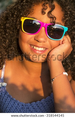 A beautiful and happy mixed race African AMerican female girl child wearing sunglasses and cowboy hat on vacation in golden sunshine - stock photo