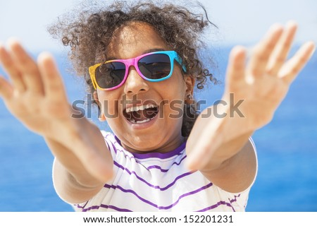 A beautiful and happy mixed race African American female girl child wearing sunglasses in bright sunshine on vacation in front of a blue tropical sea laughing & reaching to camera - stock photo