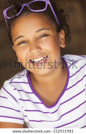 A beautiful and happy smiling mixed race African American female girl child wearing sunglasses in golden sunshine and laughing - stock photo