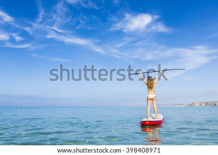 A beautiful and happy woman with arms up and learning paddle-surf - stock photo