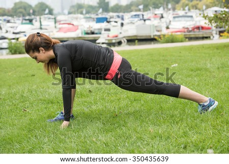 A beautiful and healthy girl doing pre exercie in a trendy sportswear inside a park in the early morning. A few boats is seen in the background of the image. - stock photo