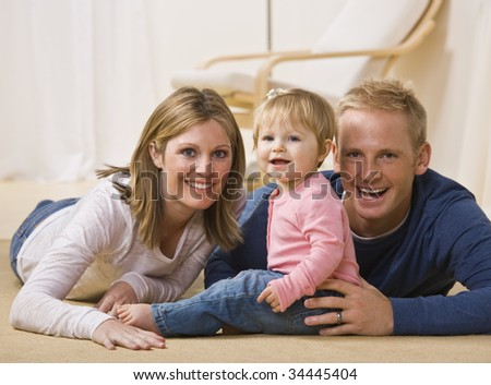 A beautiful and young couple pose with their young daughter as they all smile at the camera.  Horizontally framed shot. - stock photo