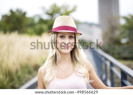 A Beautiful and young girl in a hat walking in the evening city