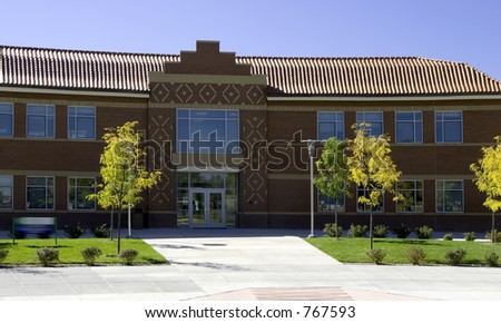 A beautiful architecturally designed private high school with red tile roof and brick. - stock photo
