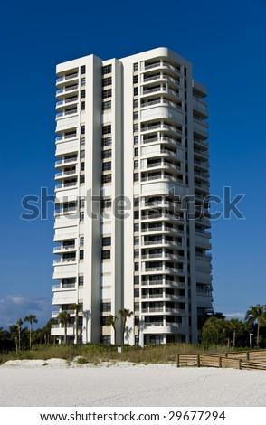 A beautiful Art Deco inspired condominium tower, over a deep blue sky. - stock photo