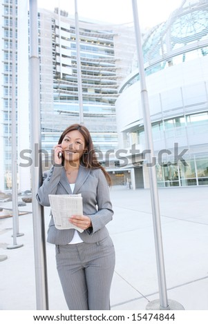 A beautiful asian business woman on cell phone at office building - stock photo
