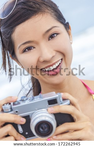 A beautiful Asian Chinese girl or young woman wearing bikini at a beach looking happy taking pictures or photographs with a retro digital camera - stock photo