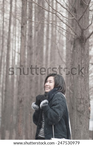 A beautiful asian girl in winter pine forest.