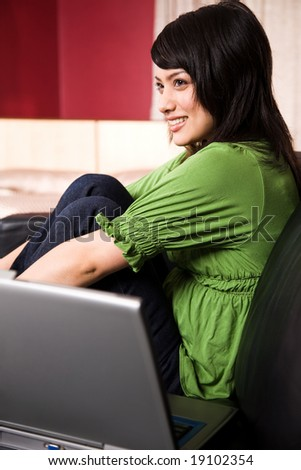 A beautiful asian girl relaxing on the sofa at home - stock photo