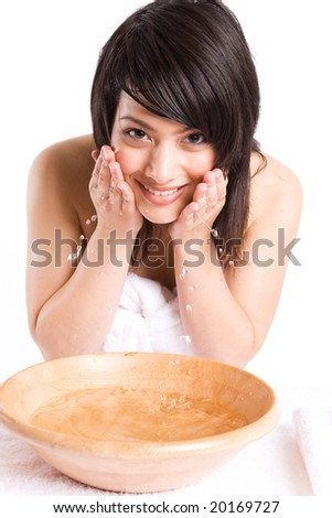 A beautiful asian girl washing face at a spa - stock photo