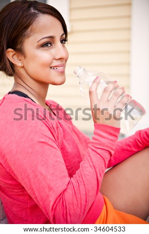 A beautiful asian woman drinking water after exercise - stock photo