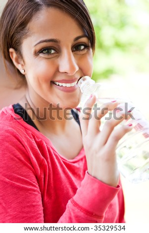 A beautiful asian woman drinking water after exercise