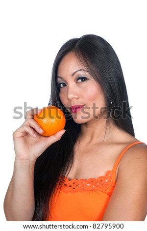 A beautiful Asian woman gets ready to eat an orange. - stock photo
