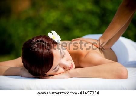 A beautiful asian woman getting a massage outdoors - stock photo