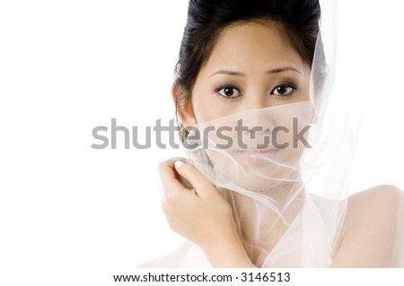 A beautiful asian woman holding her veil across her face on white background