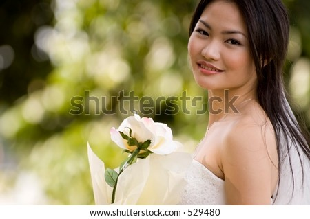 A beautiful asian woman poses in her wedding gown outside