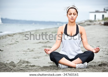 A beautiful asian woman practices yoga at a beach