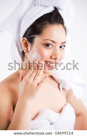 A beautiful asian woman putting on lotion on her face