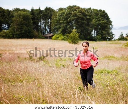 A beautiful asian woman running in a park - stock photo
