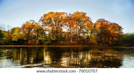 A beautiful autumn landscape with water and colorful trees.