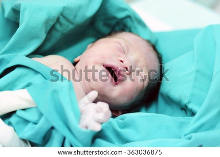 A beautiful baby girl few seconds after the birth - stock photo