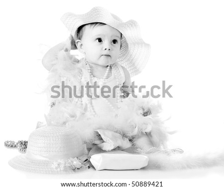 A beautiful baby girl gussied up with a fancy hat, beads and boas.  Isolated on white.
