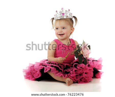 A beautiful baby girl happily holding a large flower while wearing a crown and her pink princess dress.  Isolated on white. - stock photo
