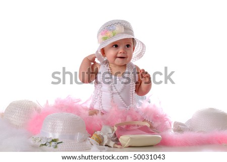 A beautiful baby girl in a fancy hat and surrounded by girly things.  Isolated on white. - stock photo