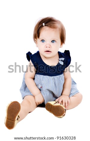 a beautiful baby girl sitting on the floor and looking towards the viewer, with her stunning blue eyes, isolated on white. - stock photo