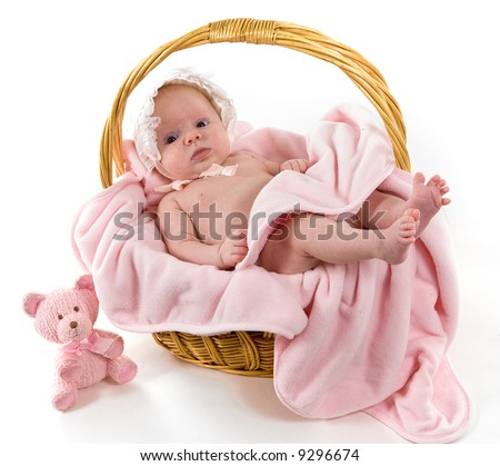 A beautiful baby girl with cute facial expression lying in a basket - two months old