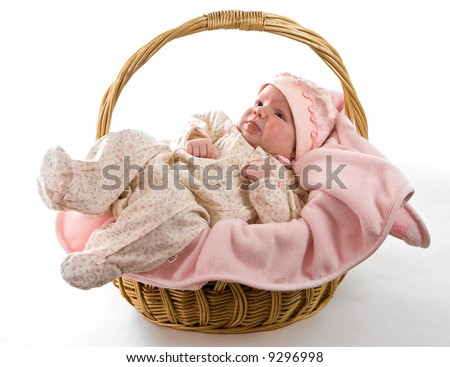 A beautiful baby girl with cute facial expression lying in a basket - two months old - stock photo