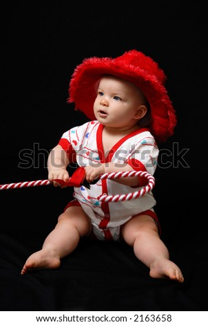 A beautiful baby portrait in a velvet Christmas hat, holding a candy-cane. - stock photo