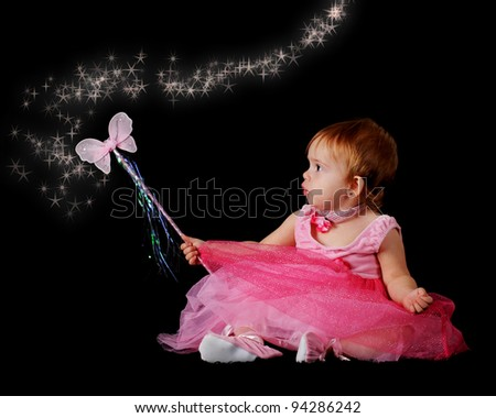 "A beautiful baby ""princess"" in pink, waving her butterfly lawn with a sparkly trail.  On a black backgound. - stock photo"