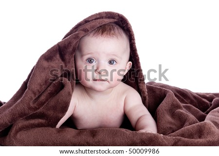 A beautiful baby under a brown towel on white background - stock photo
