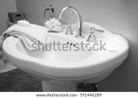 A beautiful bathroom sink with white shells, candles, and towels; a bar of white soap rests atop the towels; monochrome colortone - stock photo