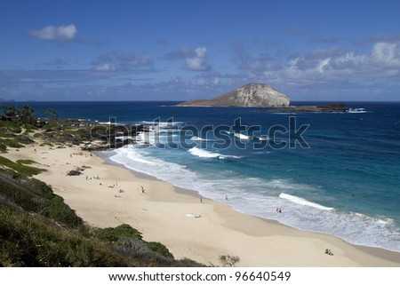 A beautiful beach on the East side of Oahu with Rabbit Island in the background. - stock photo