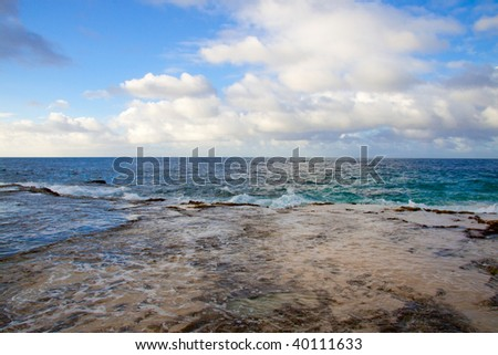 A beautiful beach with nobody in the scene as well as a dynamic sky and nice turquoise and blue tones throughout in color. - stock photo