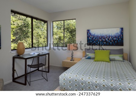 A beautiful bedroom interior with mirror and window decorated with blue bed cover. - stock photo