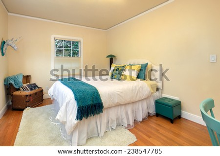 A beautiful bedroom interior with wooden floor and window decorated with blue and turquoise - stock photo